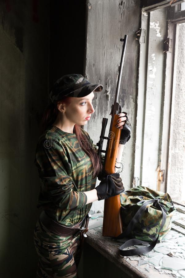 A thin red-haired girl stands at the broken window with a rifle. The girl in green camouflage with a gun. Military service for. The girl portrays a soldier royalty free stock photography