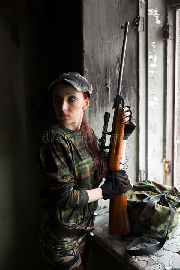 A thin red-haired girl stands at the broken window with a rifle. The girl in green camouflage with a gun. Military service for. The girl portrays a soldier royalty free stock images