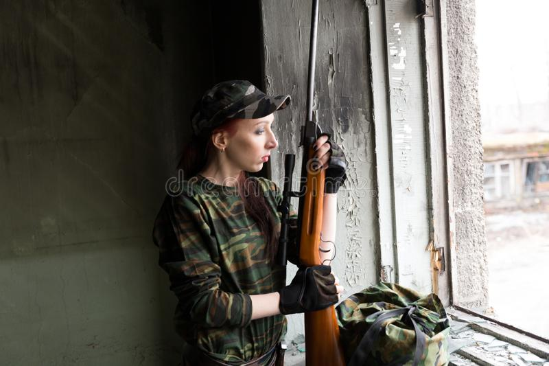 A thin red-haired girl stands at the broken window with a rifle. The girl in green camouflage with a gun. Military service for. The girl portrays a soldier stock photo
