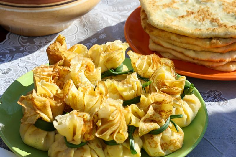 Thin ruddy pancakes with a filling wrapped in a bag and tied with green onion feathers. Pancakes are packed tightly on a large. Dish. Pancake Week Pancake Week royalty free stock photos