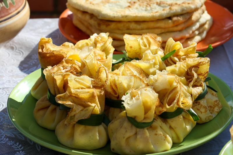 Thin ruddy pancakes with a filling wrapped in a bag and tied with green onion feathers. Pancakes are packed tightly on a large. Dish. Pancake Week Pancake Week stock images