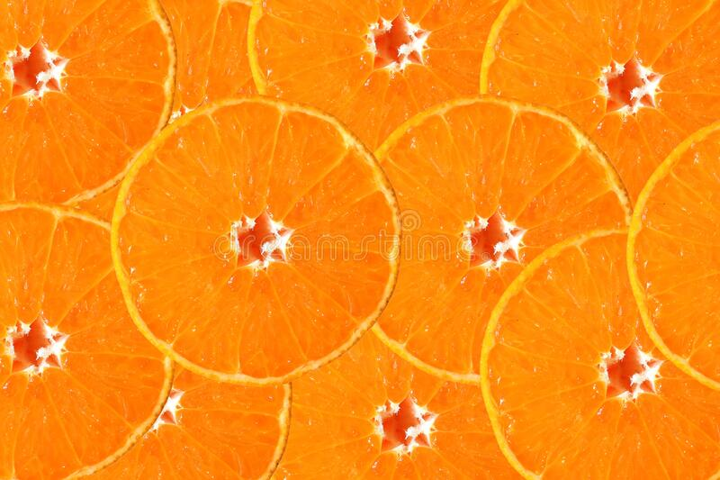 Thin slice of orange, stacked as a backdrop. royalty free stock image