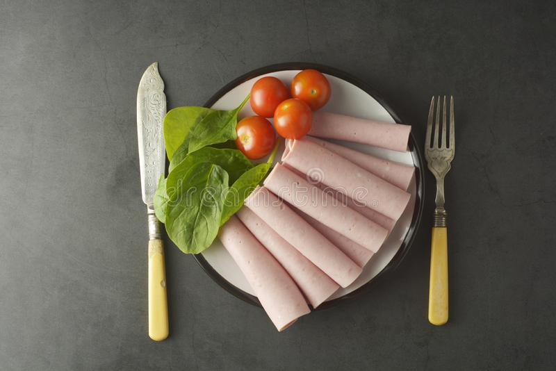 Thin slices of ham rolled on plate with fresh vegetables, dark background. Breakfast food, ingredient for sandwich. Flat lay food royalty free stock images