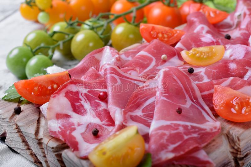 Thin slices of Italian cold cut pork Coppa and cut cherry tomatoes royalty free stock photography