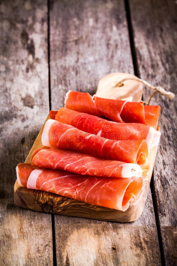 Thin slices of prosciutto on a cutting board royalty free stock photos