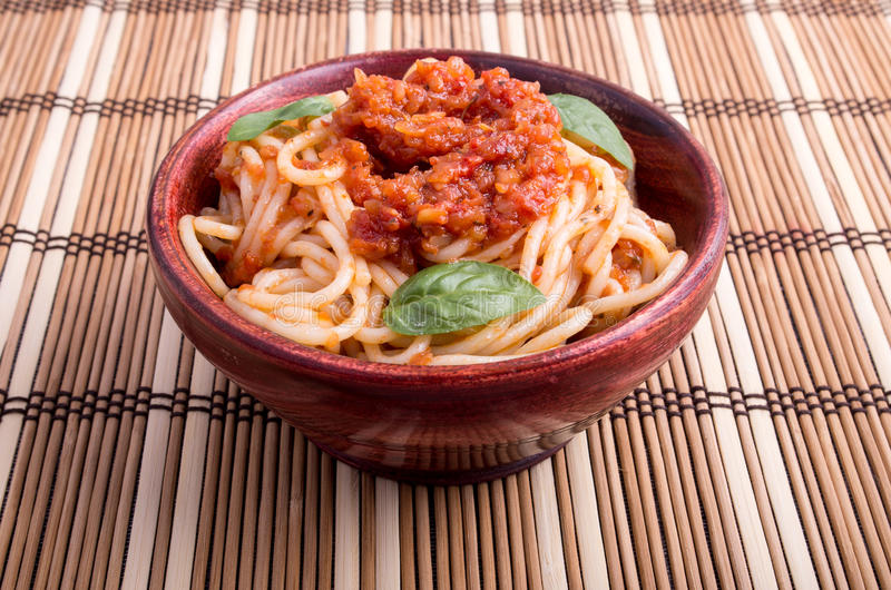 Thin spaghetti with tomato relish and basil leaves. In a brown small wooden bowl close up on a striped mat stock image