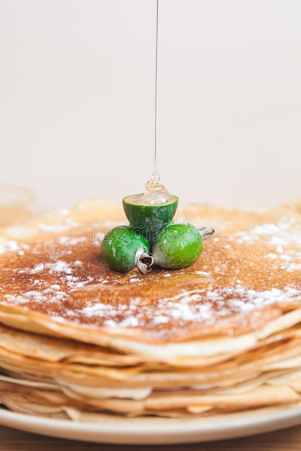 A stream of honey flows on the feijoa fruits decorating thin pancakes. A thin stream of honey flows on the feijoa fruits decorating thin pancakes stock photo