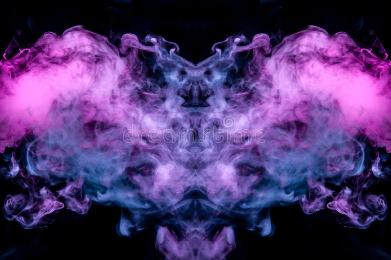 Thin streams of smoke on a black background in the neon light of a blue pink purple in the form of the head stock photography