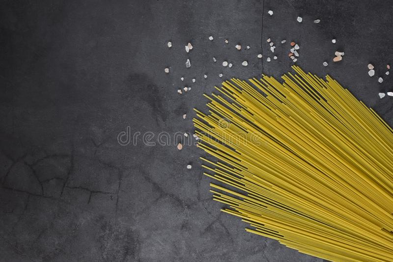 Thin threads of pasta on a neutral gray background. With picturesquely scattered grains of white and pink sea salt stock photos