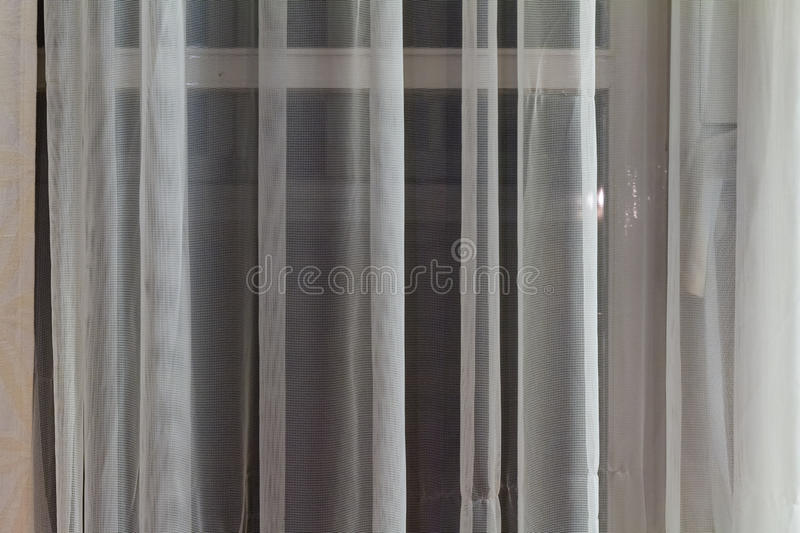 Thin translucent curtains hanging in a window stock photos