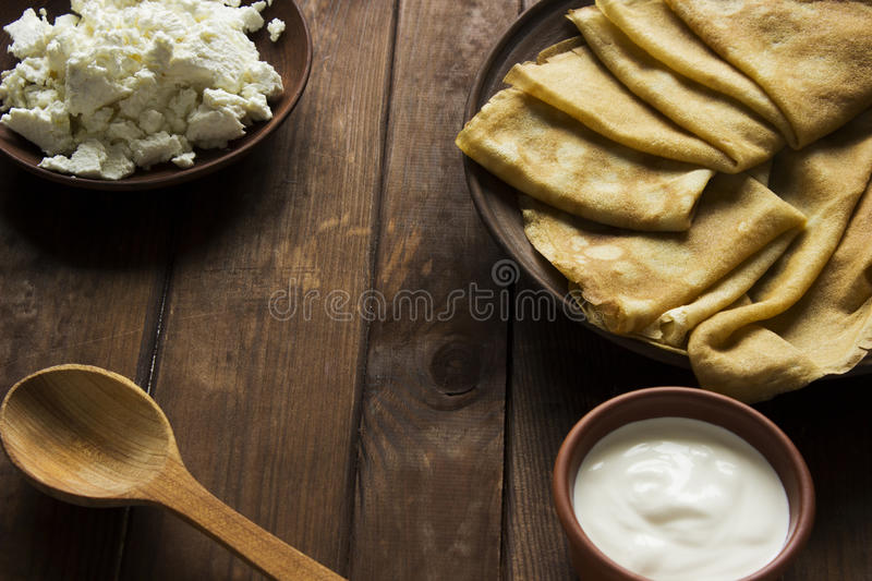 Thin Ukrainian Crepes, cottage cheese and sour creme in a crockery dishes on a dark wooden table stock image
