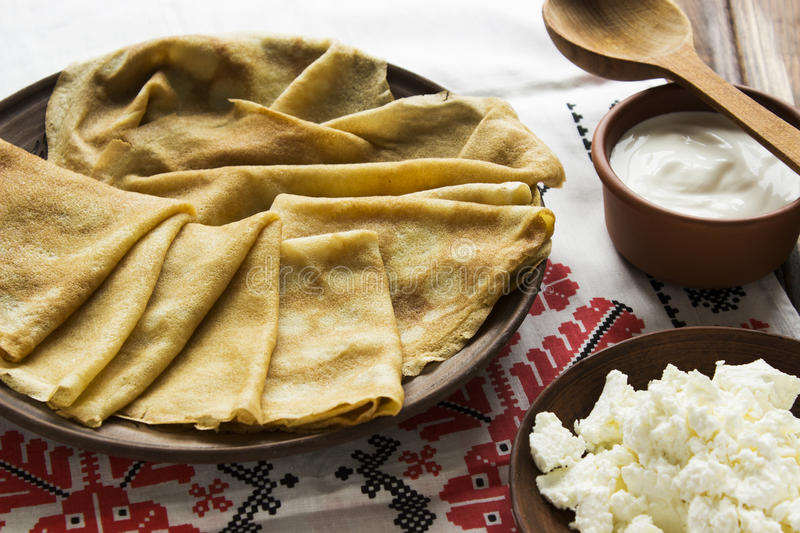Thin Ukrainian Crepes, cottage cheese, sour creme in a crockery royalty free stock photography