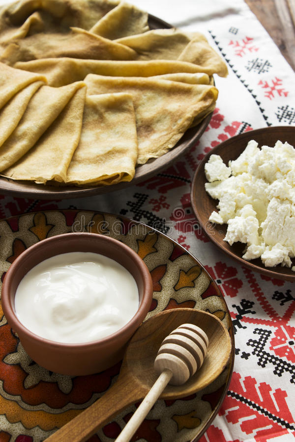 Thin Ukrainian Crepes, cottage cheese, sour creme in a crockery royalty free stock images