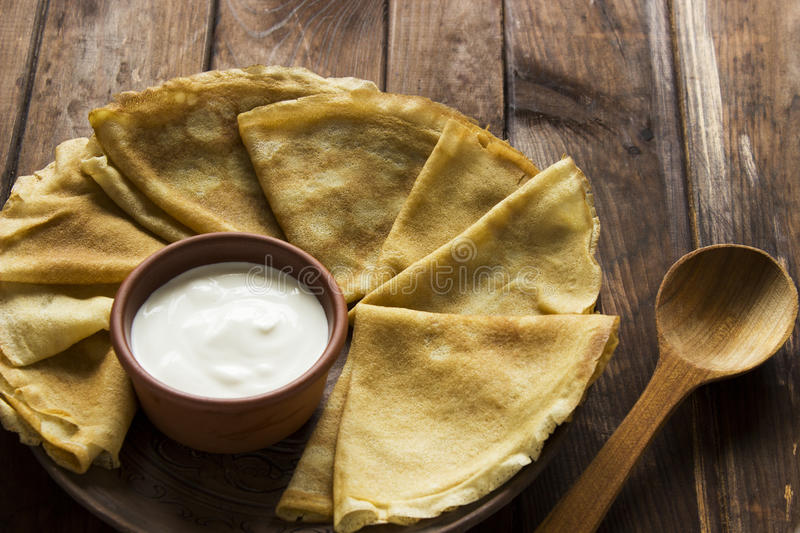Thin Ukrainian Crepes and sour creme in a crockery dishes stock photos