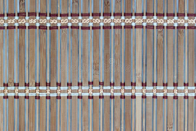 Thin wooden plank bound with colored threads. Abstract wooden background royalty free stock photos