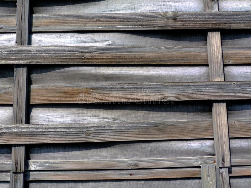 Thin woven bent wooden slat fence of horizontal strips on vertical frame with vinyl infill. Old aged vintage look. weathered texture under bright sunshine royalty free stock images