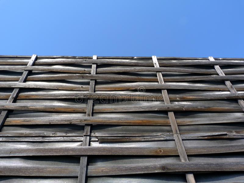 Thin woven bent wooden slat fence of horizontal strips on vertical frame with vinyl infill. Old aged vintage look. weathered texture under blue sky in bright stock image