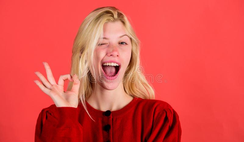 Things gonna be alright. Girl wink happy face while show ok gesture over red background. Woman satisfied with everything stock photo