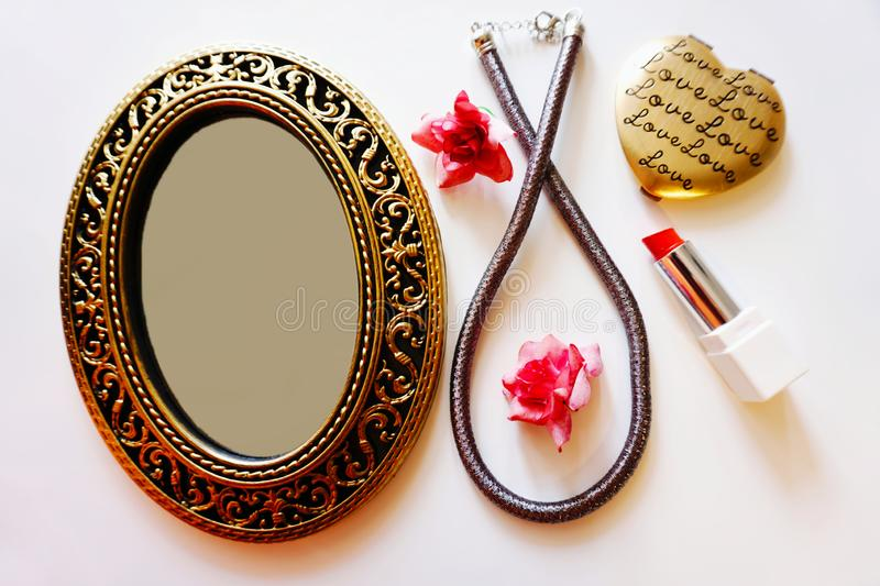 Things to beautify women. Female beauty stuff, a little mirror with an empty glass surface, a necklace and a red lipstick. Female beauty stuff, a little mirror royalty free stock photography