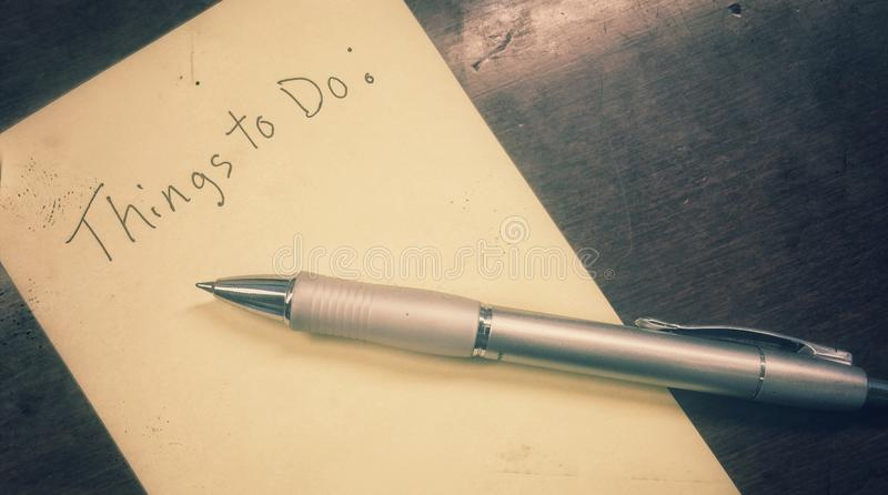 Things to do written on stionary. Things to do writing on paper with an ink pen royalty free stock image