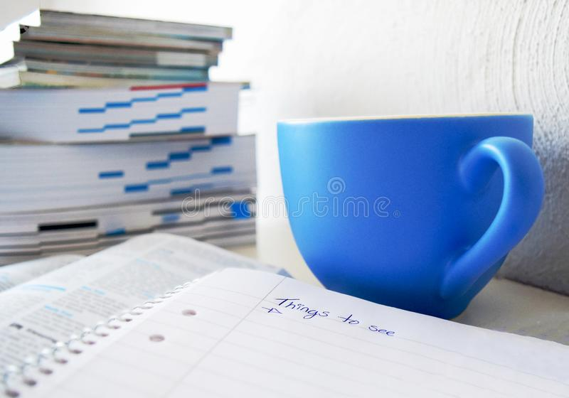 Things to see - travel planning. Travel plan with a blue cup of coffee, books and a note pad to write in stock photos