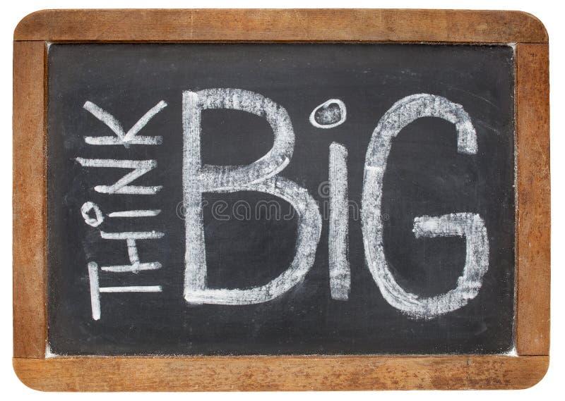 Think big on blackboard. Think big - motivational phrase - white chalk handwriting on a vintage slate blackboard royalty free stock photography