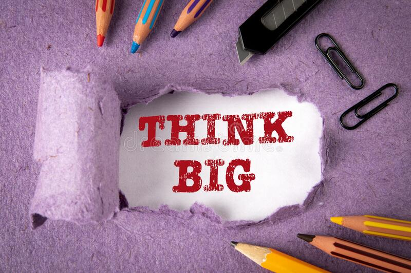 THINK BIG concept. Text under torn paper. Pencils and office supplies royalty free stock photo