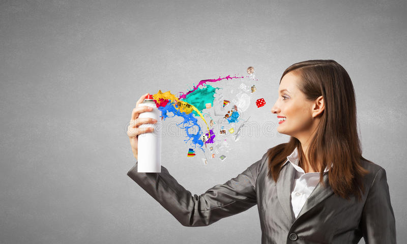 Think bright!. Businesswoman spraying colorful paint splashes from container stock photo