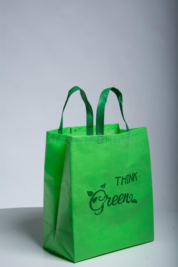 Think Green Eco Friendly Bag on table with green handle. Green Handle Loop Bag Non Woven Bags for Shopping Images for Non Woven Fabric Green D Cut Non woven tote royalty free stock photos