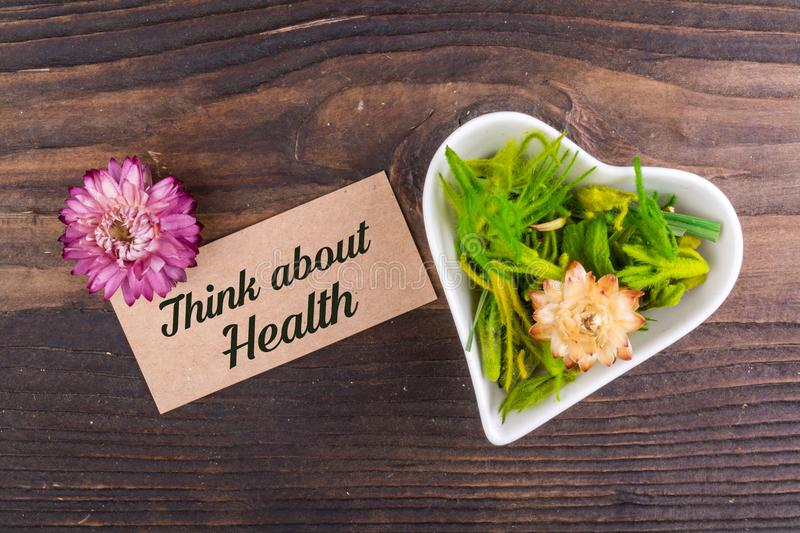 Think about Health text on card. With dried flower and heart shape bowl on wood royalty free stock image