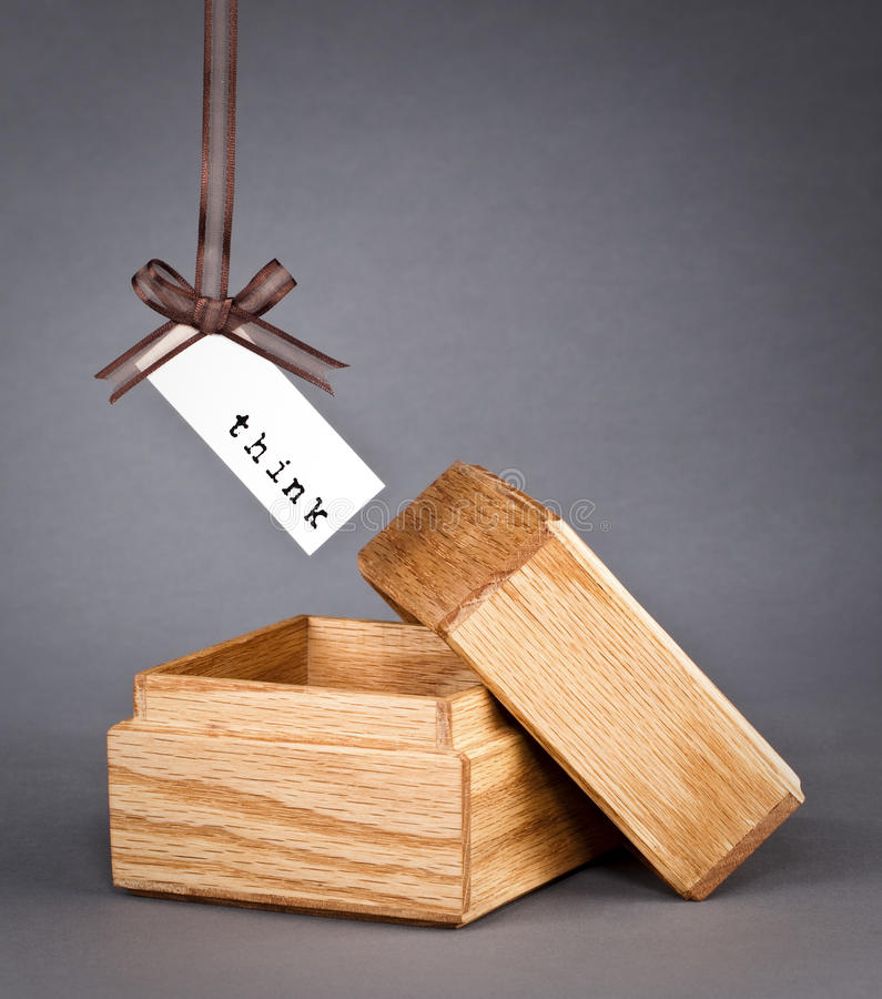 Think outside the box. Label with the word think hanging from a ribbon just outside of a little wooden box on a grey background. Brainstorming metaphor