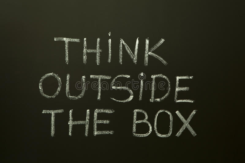 THINK OUTSIDE THE BOX on a blackboard royalty free stock images