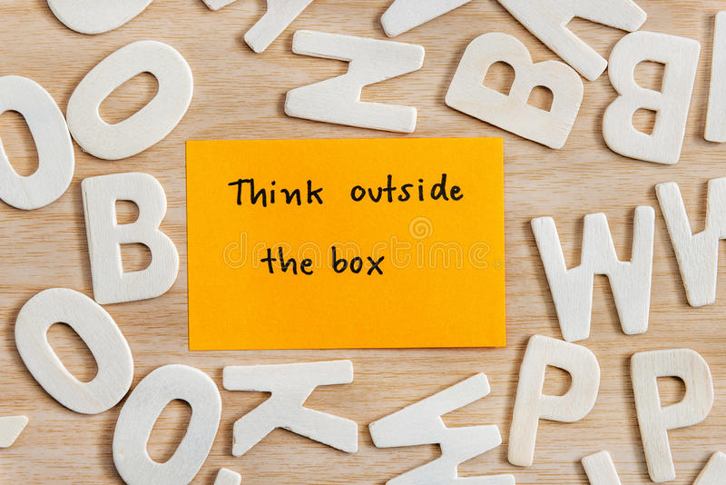 Think outside the box unique concept. Handwriting letters words think outside the box on yellow sticky note with wood alphabet on wooden table, Quote Think stock photography