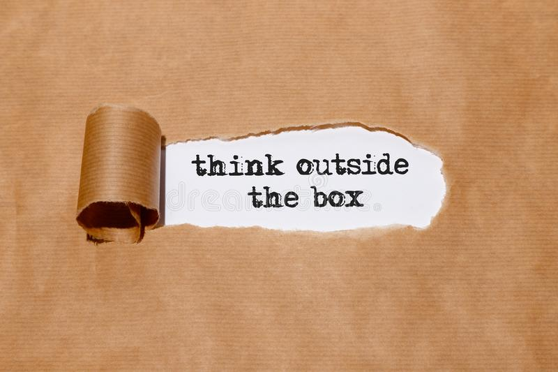 `Think outside the box` written by typewriter behind torn paper royalty free stock photography
