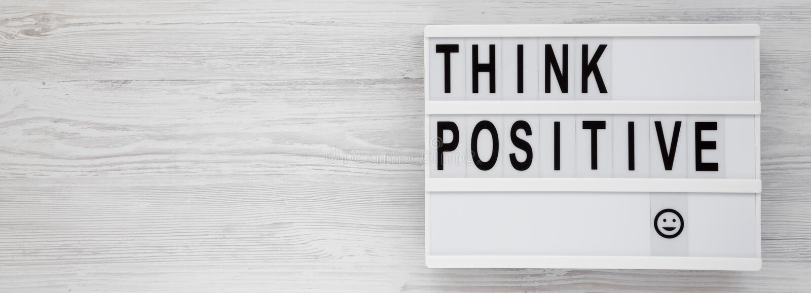 `Think positive` words on a modern board on a white wooden background, top view. Overhead, from above, flat lay. Copy space.  stock images