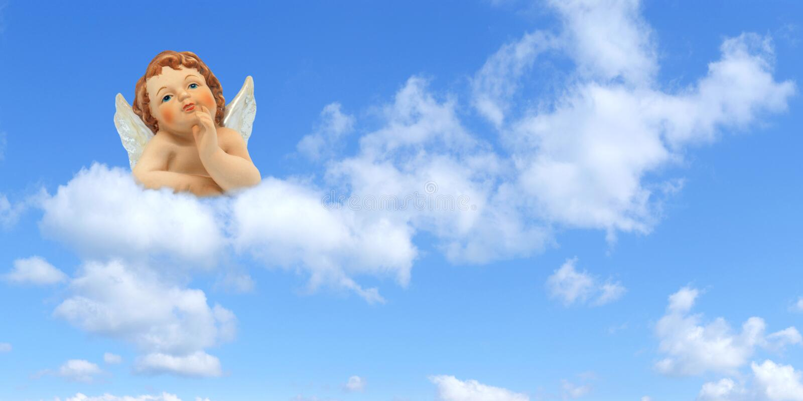Thinker angel above the clouds on a blue sky background: greeting card for christmas, baptism or communion stock image