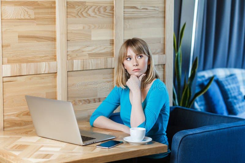 Thinkful有白肤金发的突然移动理发头发的少女自由职业者在蓝色女衬衫在咖啡馆坐并且研究膝上型计算机,有新 库存照片