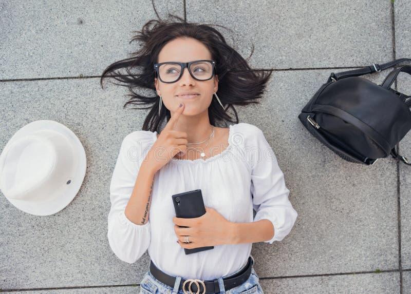 Thinkful jonge vrouw die met mobiele telefoon omhoog kijken stock foto's