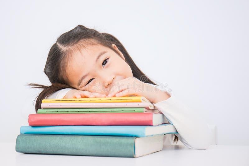 Thinkig asiático bonito pequeno da menina com a pilha de livros prontos à escola foto de stock royalty free