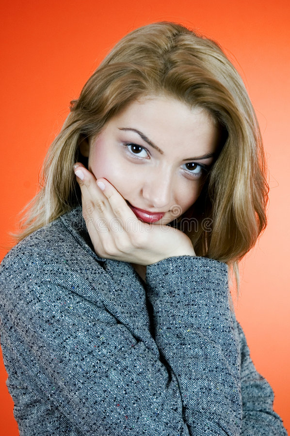 Thinking. Portrait of a smiling young woman with her chin resting in her hand. Taken in studio with an orange background royalty free stock image