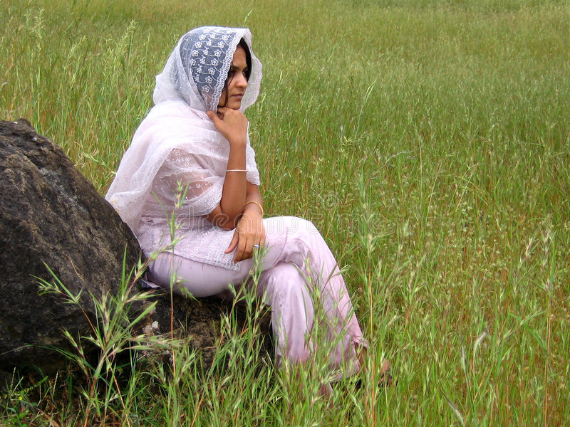 Thinking. An Indian lady sits and thinks sitting on the rock stock photos