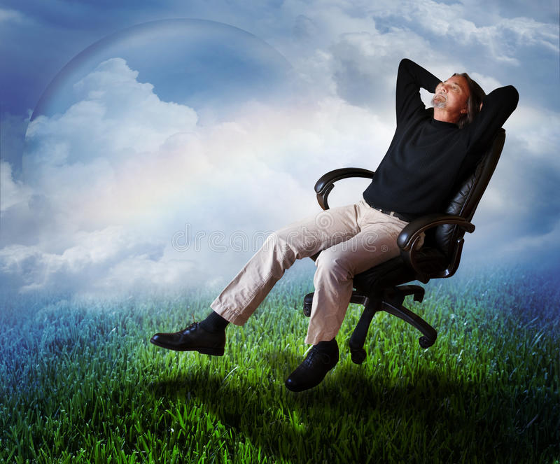 Thinking. A creative man sits back in a desk chair dreaming and looking up. Concept for creative thinking and ideas
