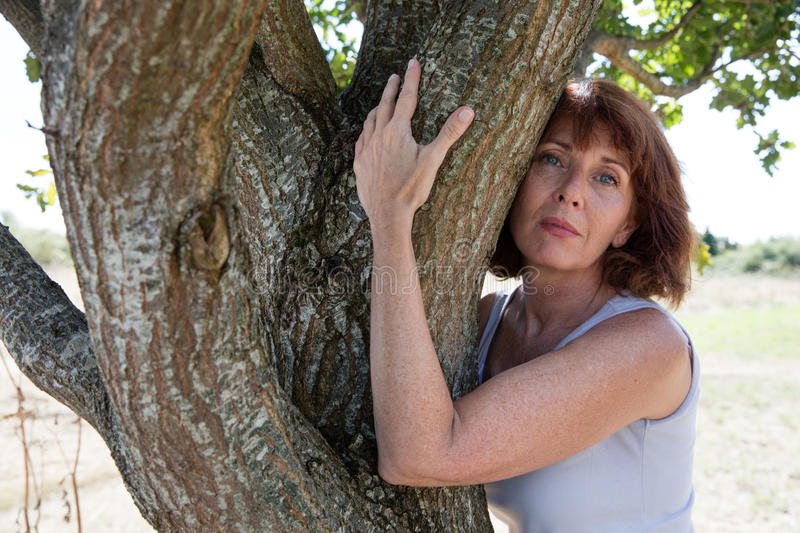 Thinking aging woman touching a tree for reinsurance. Senior green wellness - beautiful calm mature woman hugging a tree in harmony with nature for serenity and royalty free stock photo