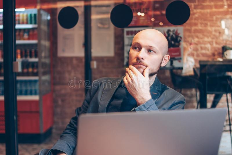 Thinking attractive adult successful bald bearded man in suit with laptop in cafe stock image