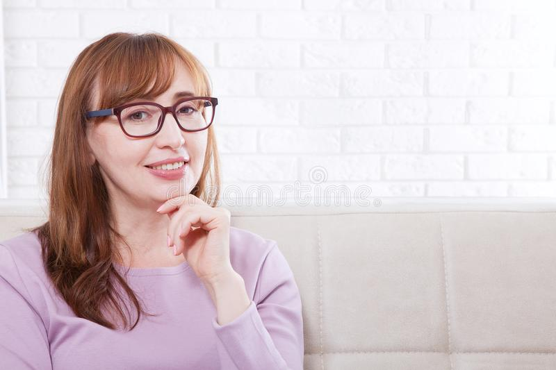 Thinking Attractive Middle Aged Woman In Glasses With Folded Arms On ...