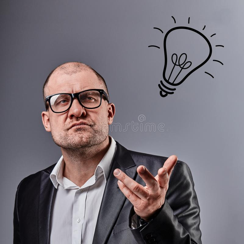 Thinking bald business man in eyeglasses discussing and have an idea showing the hand on lamp illustration on grey background. Closeup studio portrait stock photo