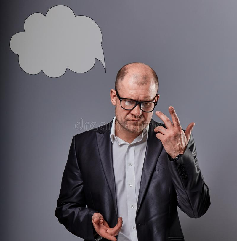 Thinking bald business man in eyeglasses and suit discussing and have an idea on grey background with empty cloud above the head. Closeup portriat stock image