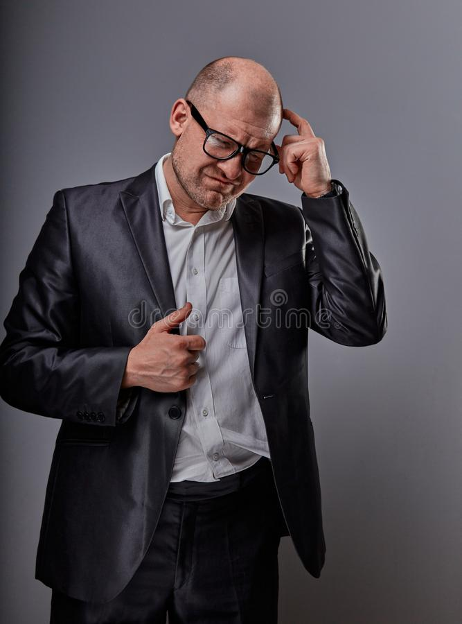 Thinking bald business man looking serious in eyeglasses having an idea and scratching the head in suit on grey background. Closeup studio portrait stock photography
