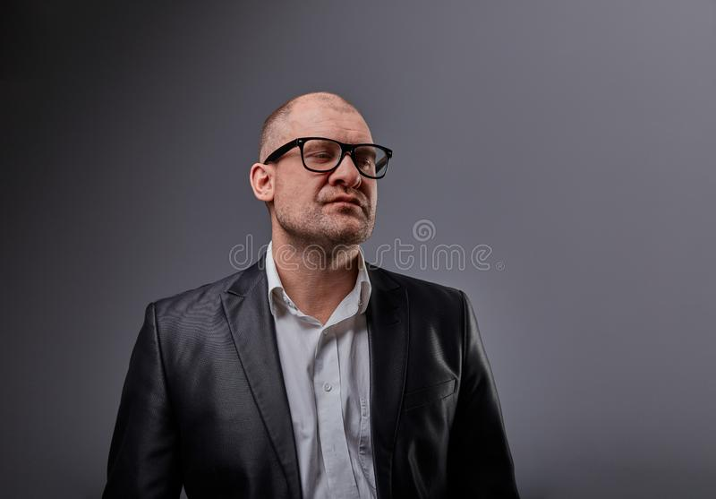 Thinking bald business man looking up serious in eyeglasses and have an idea in suit on grey background. Closeup. Studio portrait royalty free stock photo
