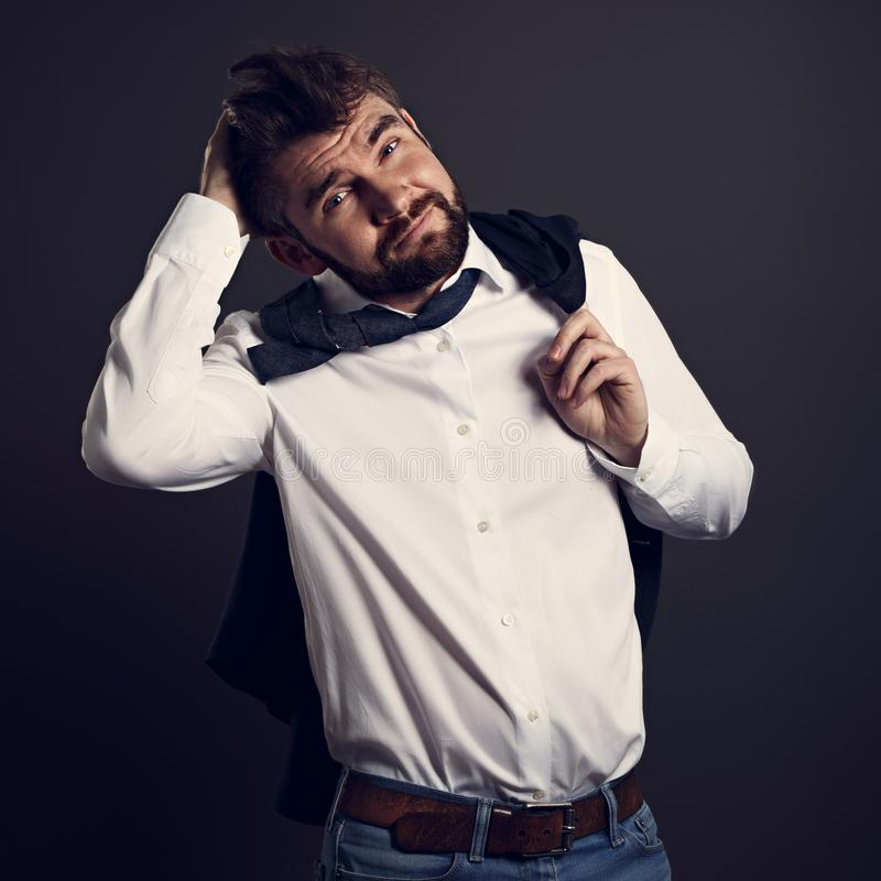 Thinking bearded emotional charismatic man in whirt shirt looking with doubt emotion face scratching the head on grey background. Closeup toned portrait stock photography